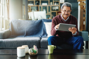 mature-man-using-his-tablet-relaxing-at-home